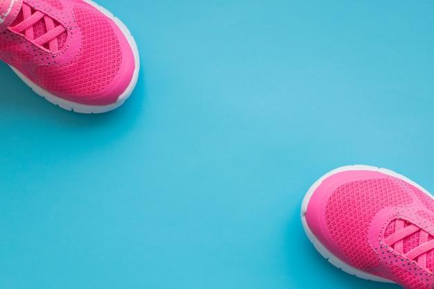 青の背景に分離されたピンクの子供トレーニングシューズ。子供服、靴、fashion.childrenのスポーツスニーカー。女の子のスポーツシューズのペア。コピースペース Premium写真