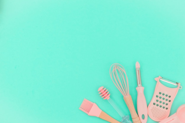 Pink kitchen utensils on neo mint background. greater, whisk and iron cooking form. top view Premium Photo