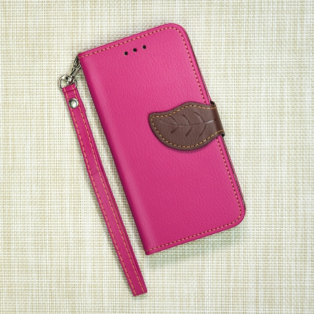 Pink leather phone case on weave background. fashion mobile phone cover. Premium Photo