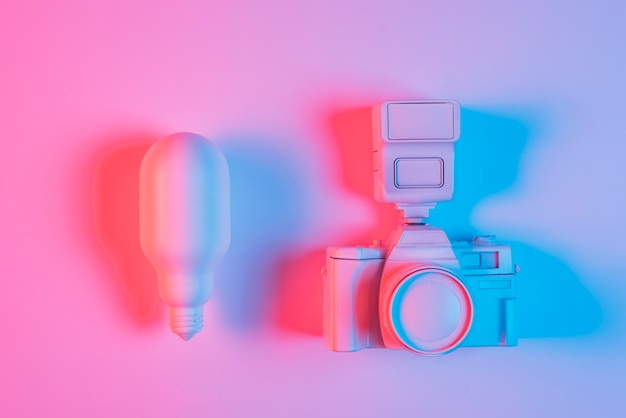 Pink light bulb and camera with blue light on pink surface Free Photo