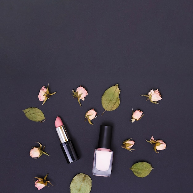 Pink lipstick and nail varnish bottle surrounded with pink rose buds and leaves on black background Free Photo