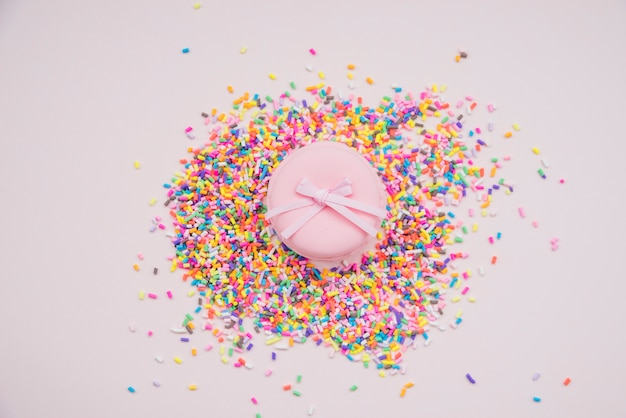 Pink macarons over the colorful sprinkles on colored background Free Photo