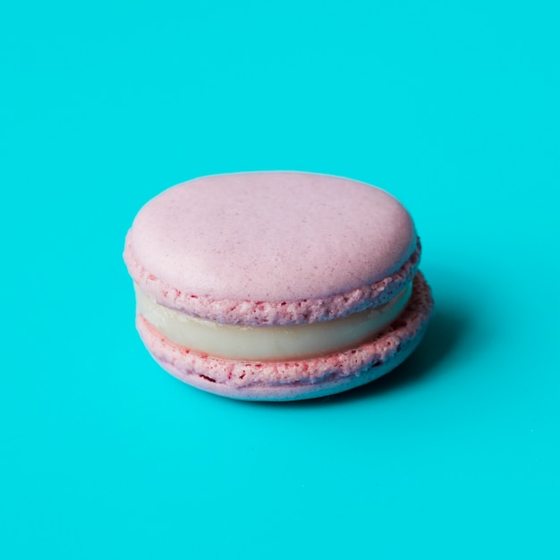 Pink macaroon with cream on blue background Free Photo