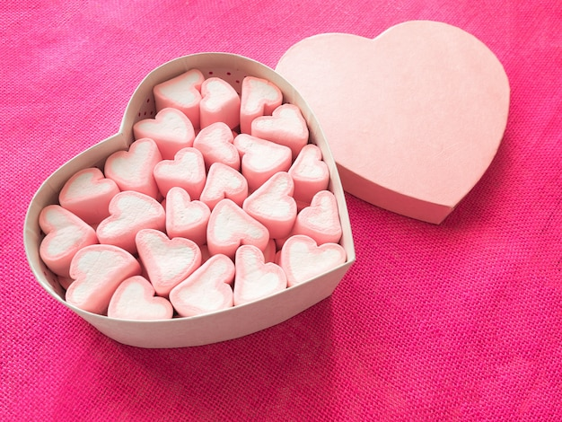 Pink marshmallow in a gift box in form of heart on pink canvas Premium Photo
