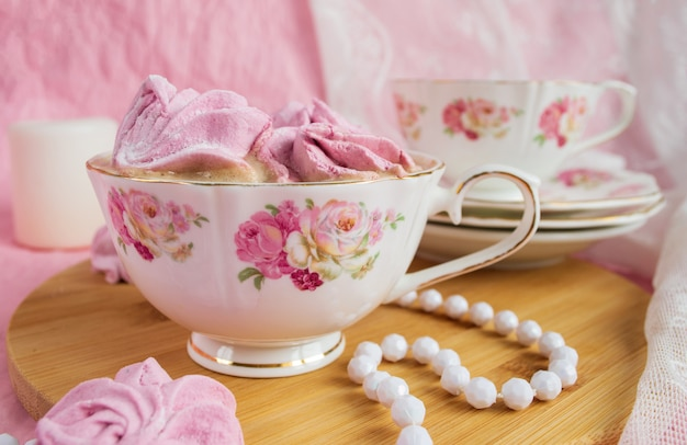 Pink marshmallows in a cup with coffee. shabby style. Premium Photo