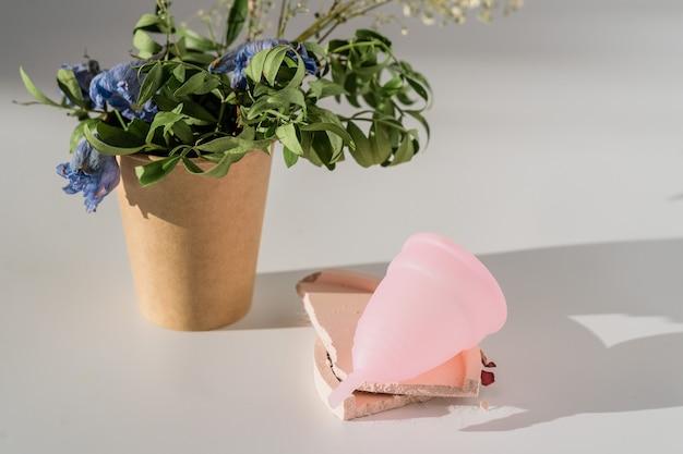日光と影と白い背景の上のピンクの月経カップ。 Premium写真