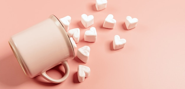 A pink mug lies on its side against a pink surface, light pink marshmallows sprinkled from it in the form of hearts Premium Photo