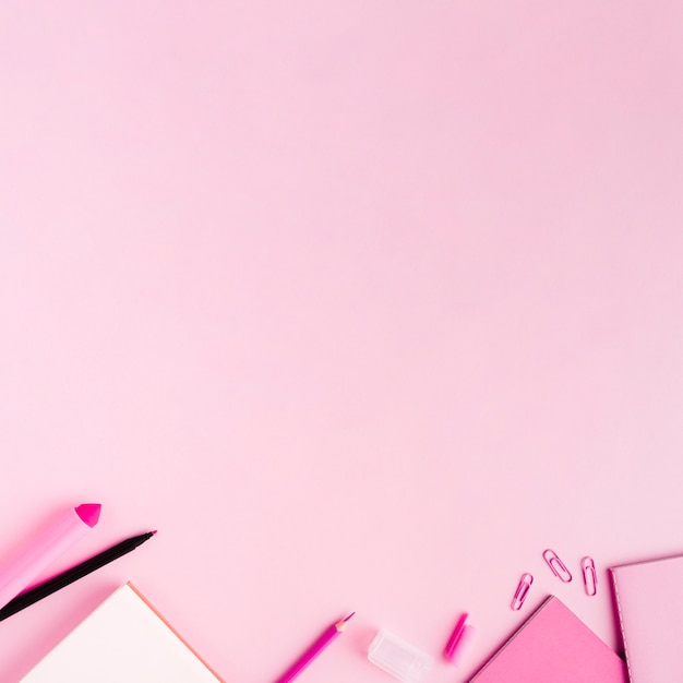 Pink office utensils on colored surface Free Photo