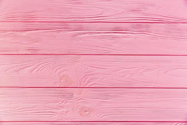 Окрашенная в розовый цвет шероховатая деревянная поверхность Premium Фотографии