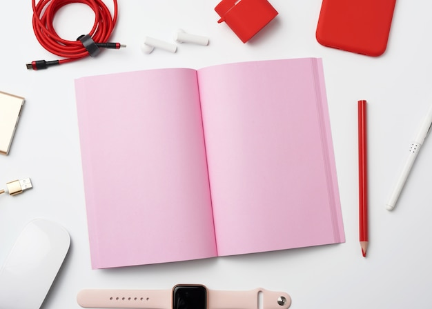 Pink paper notebook, power bank with cable, red smartphone, headphones, wireless mouse and smart watch Premium Photo