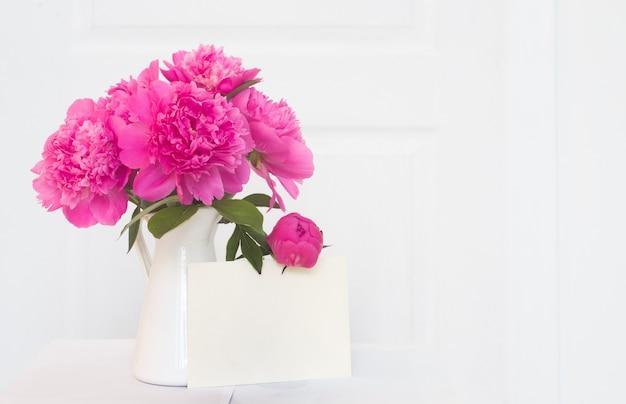 白いエナメルを塗られた花瓶のピンクの牡丹。インテリアデザインの美しい花。招待状、花瓶、室内装飾の白い牡丹のホワイトペーパー 無料写真
