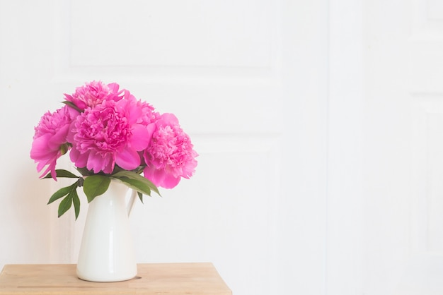 Pink peonies in white enamelled vase. flowers bouquet on wooden table in white provence interior. home interior with decor elements Free Photo