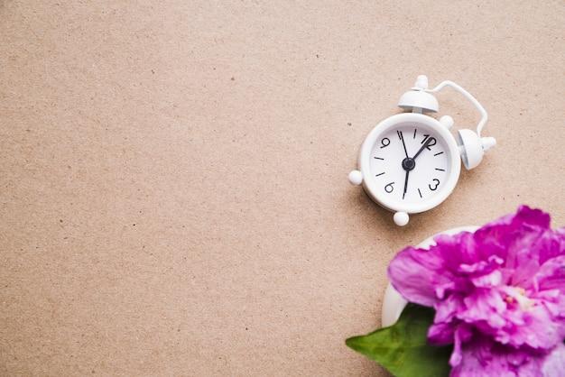 종이 질감 골 판지 배경에 흰색 알람 시계와 꽃병에 분홍색 모란 꽃 무료 사진