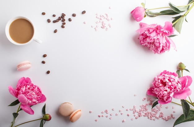 Pink peony flowers and a cup of coffee on white Premium Photo