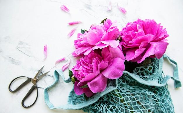 白い大理石のひもバッグのピンクの牡丹。 Premium写真