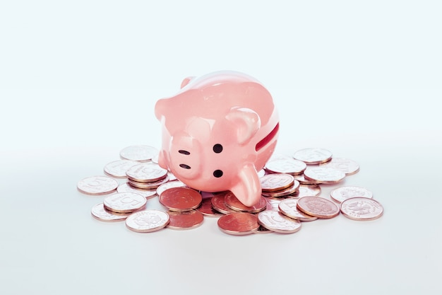 Pink piggy bank and coins isolated on white Premium Photo