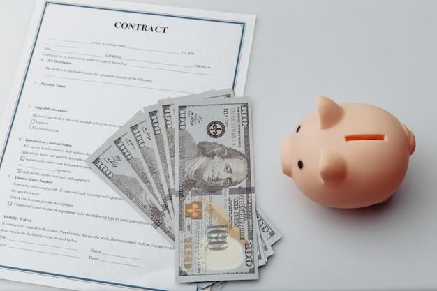 ピンクの貯金箱、白いテーブルの上の契約とお金。経済と経営の財務概念。 Premium写真
