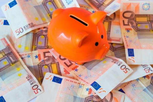 Pink piggy bank on money, euros bills Free Photo