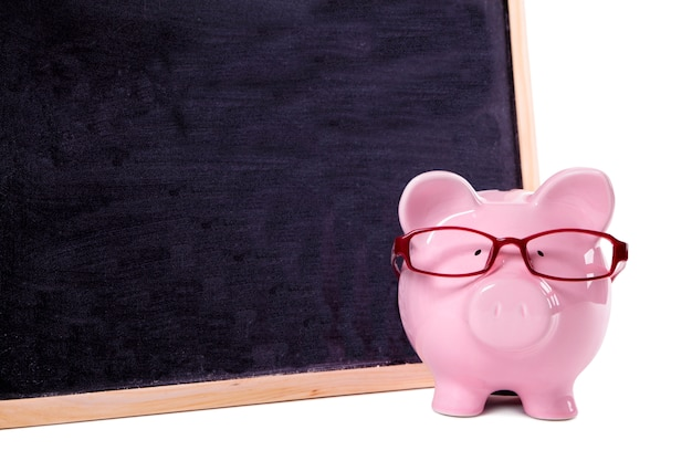 Pink piggy bank with glasses standing next to a blackboard Free Photo