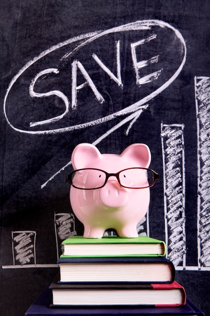 Pink piggy bank with glasses standing on books next to a blackboard with savings growth chart. Free Photo