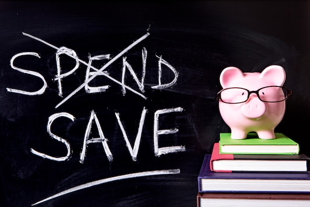 Pink piggy bank with glasses standing on books next to a blackboard Premium Photo