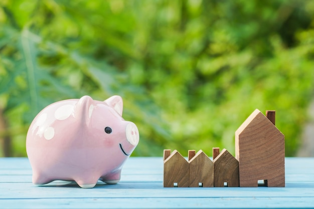 Pink piggy bank and wood house on green natural background Premium Photo