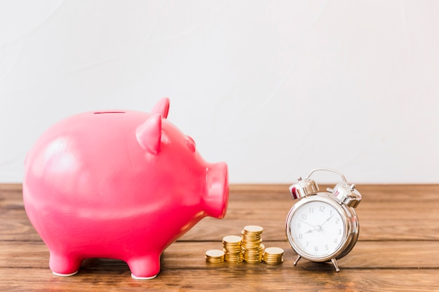 Pink piggybank near stacked coins and alarm clock Free Photo