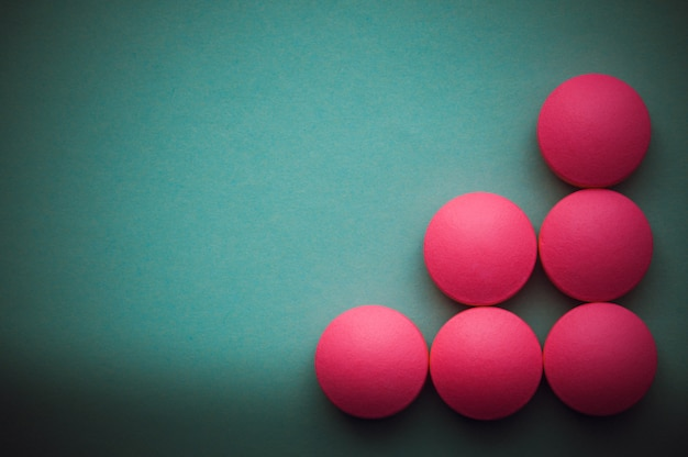 Pink pills laid out on a green background. Premium Photo