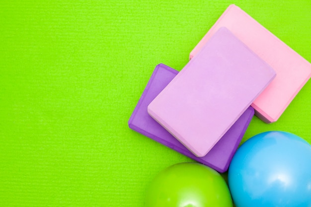Pink and purple blocks, balls and dumbbell on green mat. Premium Photo