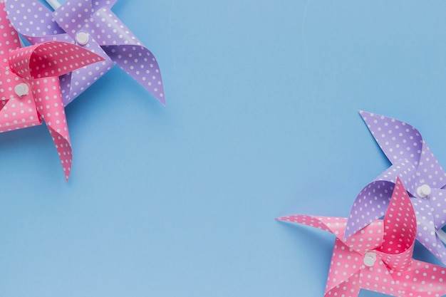 Pink and purple polka dotted pinwheel arrange at the corner of blue backdrop Free Photo