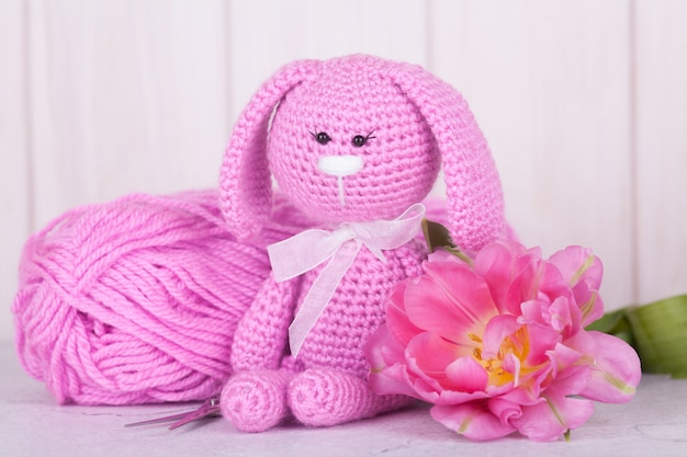 Pink rabbit with tulips. st. valentine's day decor. knitted toy, amigurumi, Premium Photo