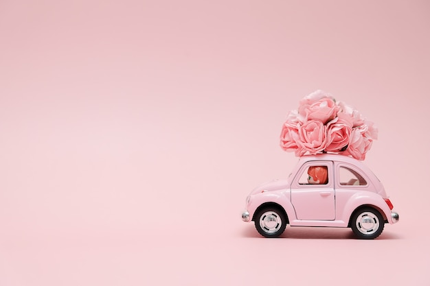 Pink retro toy car delivering bouquet of flowers Premium Photo
