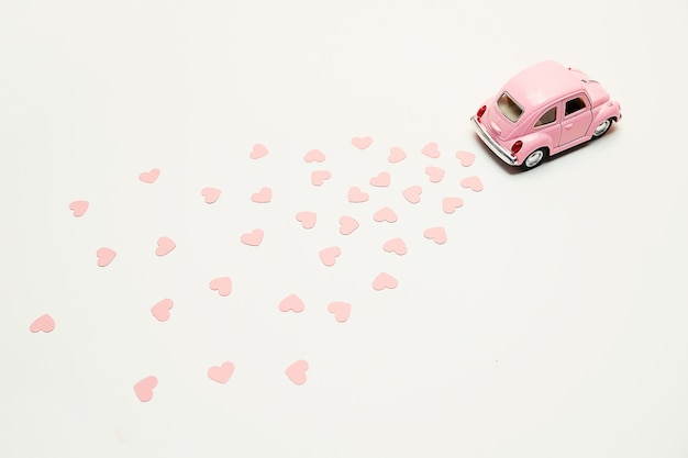 Pink retro toy car delivering hearts on pink background. valentine's day card Premium Photo