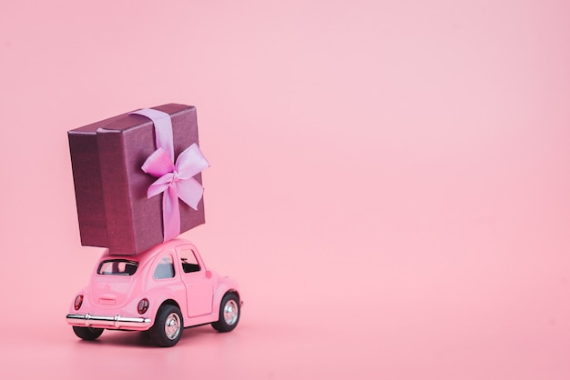 Pink retro toy car delivers a gift box on pink background. february 14 postcard, valentine's day. flower delivery.women's day Premium Photo