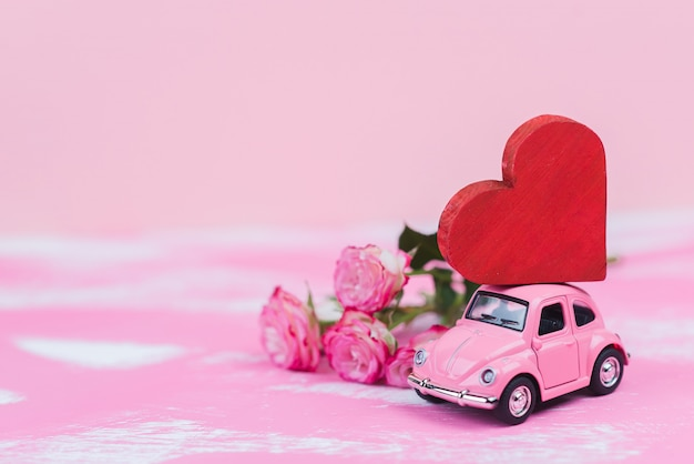 Pink retro toy car delivers a red hart on pink background. february 14 postcard, valentine's day. flower delivery.women's day Premium Photo