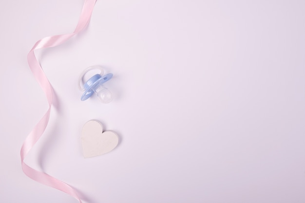 Pink ribbon and pacifier copy space Free Photo