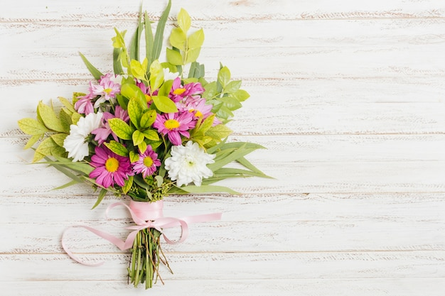 Pink ribbon tied with flower bouquet on wooden desk Free Photo