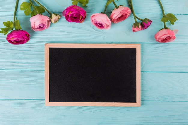 Pink rose flowers with chalkboard on wooden table Free Photo