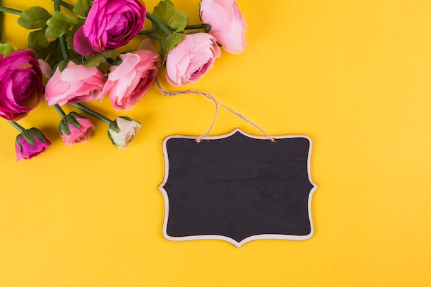 Pink rose flowers with small chalkboard on yellow table Free Photo