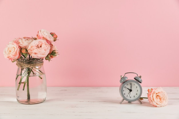 Pink rose in the glass jar and gray vintage small alarm clock on wooden desk against pink background Premium Photo