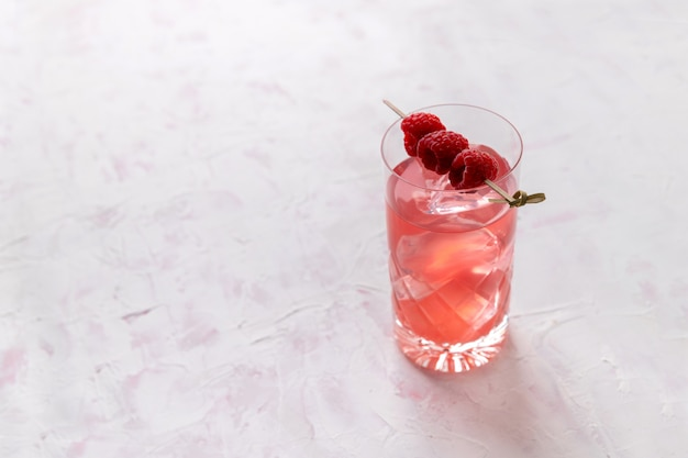 Pink rose iced cocktail with raspberry in crystal glass on table Premium Photo