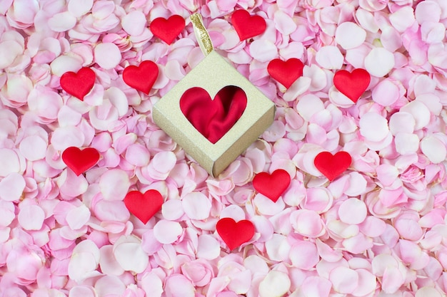 Розовые лепестки роз, атласные сердечки и подарочная коробка Premium Фотографии