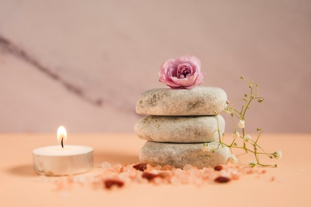 Pink rose over the stack of spa stones with illuminated candle; himalayan salts and baby's-breath flowers on colored background Free Photo