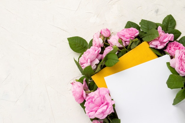 Pink roses are lined around a book with a yellow cover on a light background Premium Photo