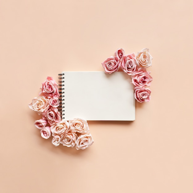 Pink roses are lined around a notebook on a light pink background. Free Photo