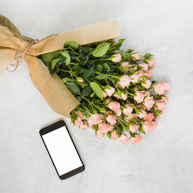 Pink Roses Bouquet Wrapped In Brown Paper And Smartphone On Concrete