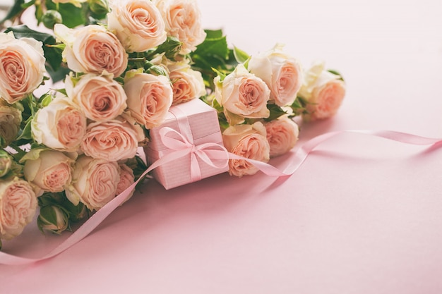 Pink roses flowers and gift or present box pink background. Premium Photo