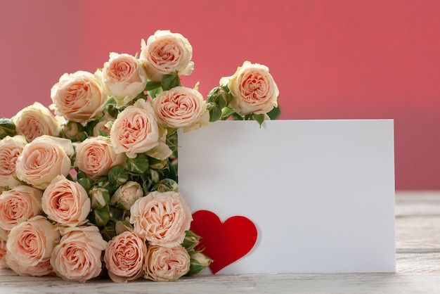 Pink roses flowers with gift card and red paper heart on pink Premium Photo