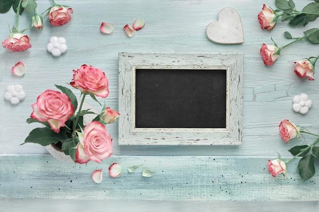 Розовые розы на светлой мятной стене с сердечками и лаком для доски Premium Фотографии