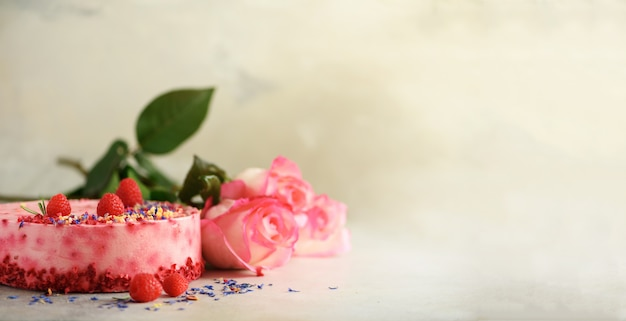 Pink roses and raspberry cake with fresh berries, rosemary, dry flowers on concrete background. Premium Photo